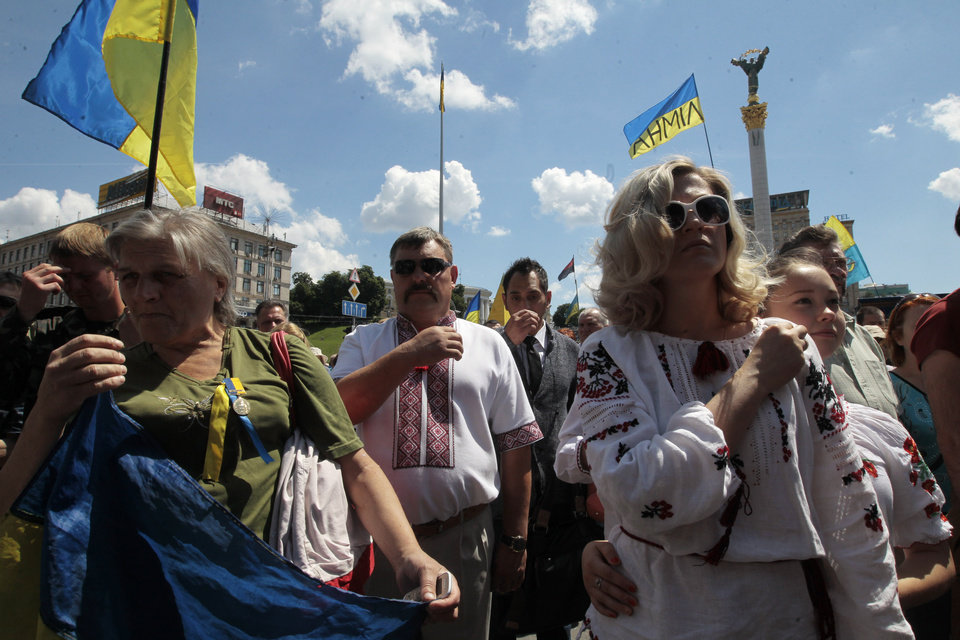 Photo - People pray during a rally in Independence Square in Kiev, Ukraine, Sunday, June 29, 2014. Hundreds of people have come on Sunday morning to the presidential administration to demand a stop to the cease fire on the eastern part of Ukraine. According to soldiers of the Donbass battalion, the other side hasn't stopped attacks and around 20 soldiers were killed during the last week that suppose to be a pause in active fighting. (AP Photo/Sergei Chuzavkov)