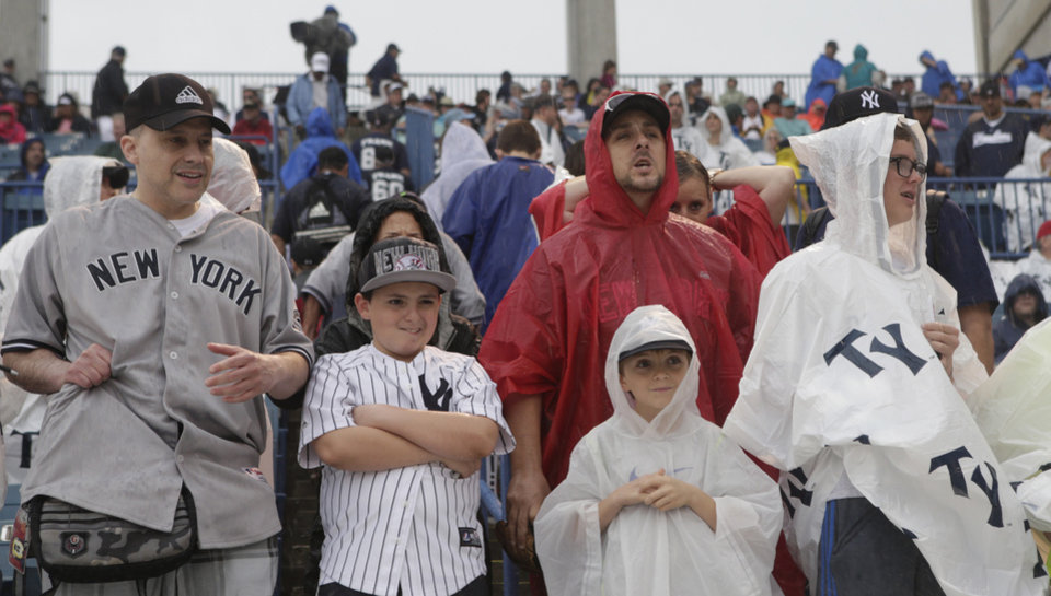 Photo - Rain gear-covered New York Yankees fans wait above the Yankees dugout before the Yankees final spring exhibition baseball game, against the Miami Marlins, was canceled due to heavy rain in Tampa, Fla., Saturday, March 29, 2014. (AP Photo/Kathy Willens)