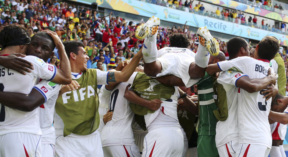 Photo - Costa Rican players celebrate after Bryan Ruiz scored his side's first goal during the group D World Cup soccer match between Italy and Costa Rica at the Arena Pernambuco in Recife, Brazil, Friday, June 20, 2014.  (AP Photo/Ricardo Mazalan)
