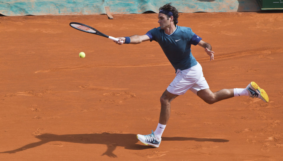 Photo - Roger Federer of Switzerland, returns the ball to Lukas Rosol of the Czech Republic during their third round match of the Monte Carlo Tennis Masters tournament in Monaco, Thursday, April 17, 2014. Federer won 6-4 6-1. (AP Photo/Michel Euler)