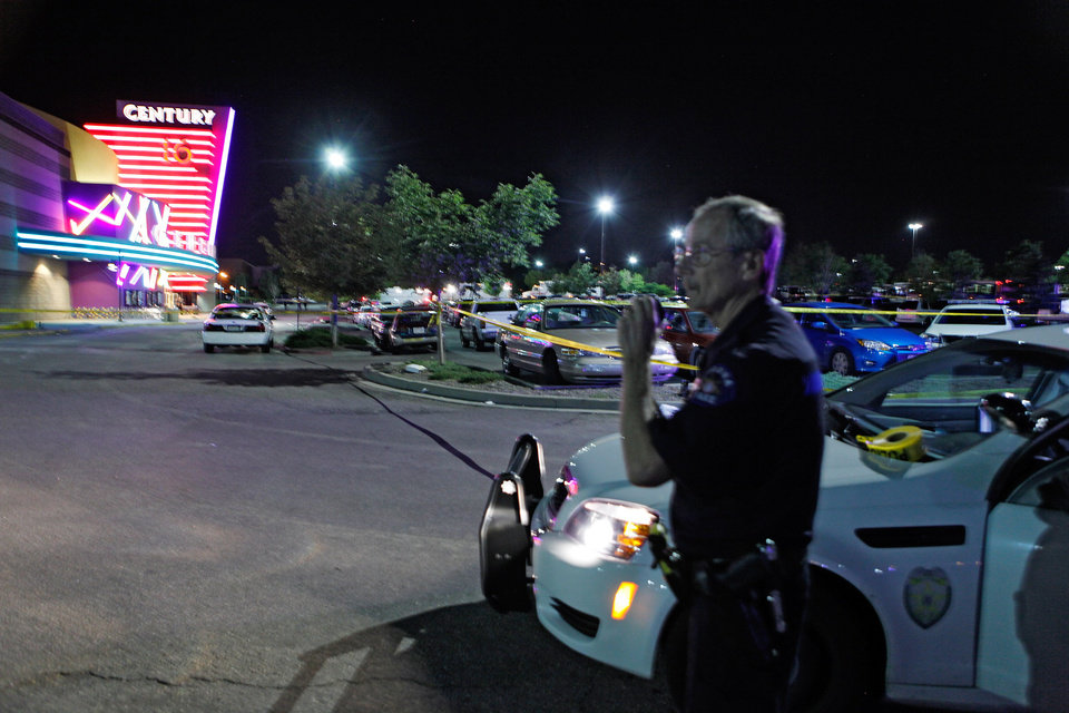 Photo - An Aurora Police officer talks on his radio outside of the Century 16 theater at Aurora Mall where as many as 14 people were killed and many injured at a shooting at the Century 16 movie theatre in Aurora, Colo., Friday, July 20, 2012. (AP Photo/Ed Andrieski) ORG XMIT: COEA101