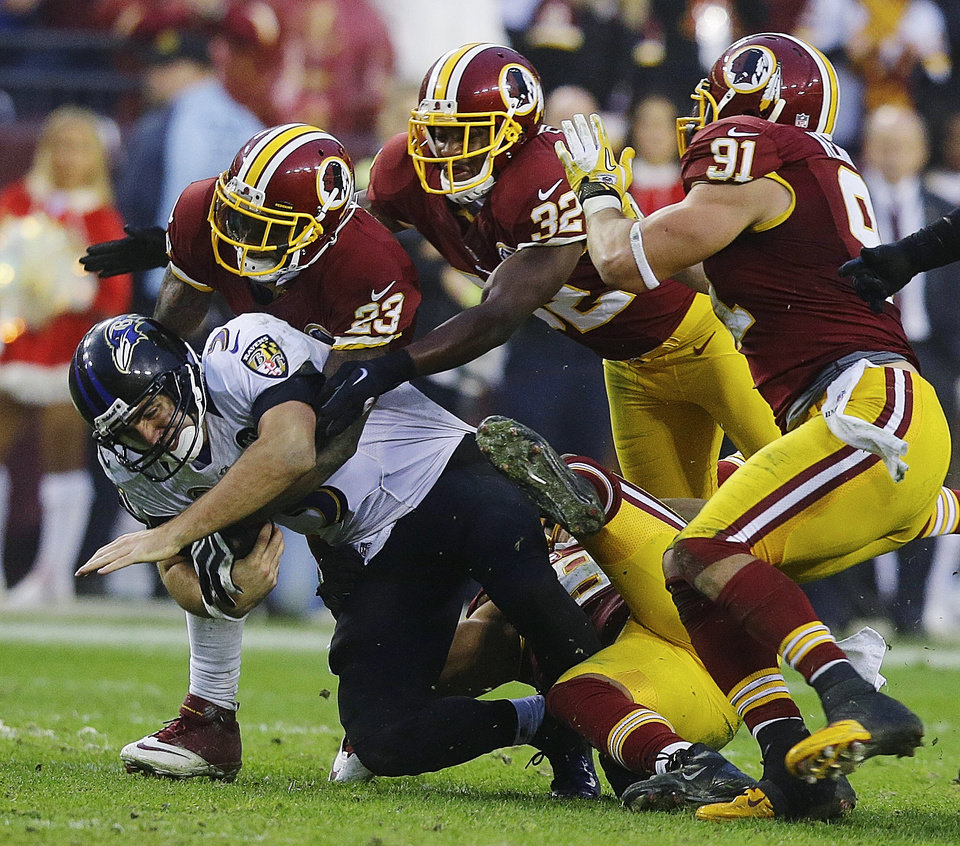 Photo - Baltimore Ravens quarterback Joe Flacco is sacked by Washington Redskins cornerback DeAngelo Hall (23), defensive back Jordan Pugh (32) and outside linebacker Courtney Upshaw during overtime in an NFL football game in Landover, Md., Sunday, Dec. 9, 2012. The Redskins won 31-28. (AP Photo/Alex Brandon)