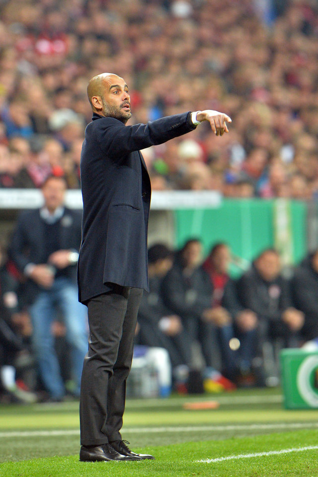 Photo - Munich head coach Pep Guardiola points during the German soccer cup, DFB Pokal, semifinal match between FC Bayern Munich and FC Kaiserslautern in the Allianz Arena in Munich, Germany, on Wednesday, April 16. 2014. (AP Photo/Kerstin Joensson)