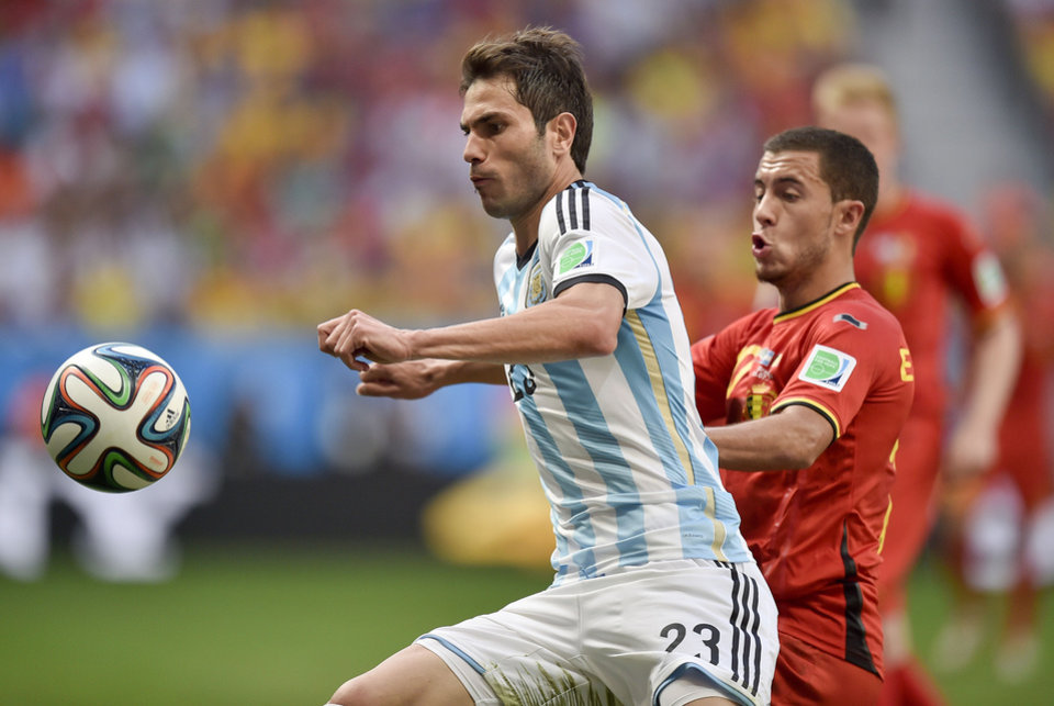 Photo - Argentina's Jose Maria Basanta, left, is challenged by Belgium's Eden Hazard during the World Cup quarterfinal soccer match between Argentina and Belgium at the Estadio Nacional in Brasilia, Brazil, Saturday, July 5, 2014. (AP Photo/Martin Meissner)