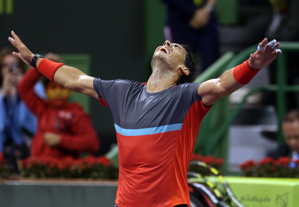 Photo - Spain's Rafael Nadal celebrates after winning the  final match of the Qatar Open tournament in Doha against France's Gael Monfils on Saturday, Jan. 4, 2014. (AP Photo/Osama Faisal)
