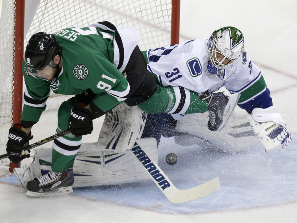 Photo - Vancouver Canucks goalie Eddie Lack (31) blocks a shot against Dallas Stars center Tyler Seguin (91) during the first period of an NHL hockey game Thursday, March 6, 2014, in Dallas. (AP Photo/LM Otero)