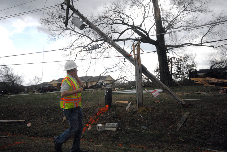 An utility worker assesses damage on to power lines in Athens, Ala., that were heavily damaged by a strong storm that swept through the area Friday, March 2, 2012.   A reported tornado destroyed several houses in northern Alabama as storms threatened more twisters across the region Friday.  (AP Photo/Lora Scripps, Athens Courier Journal) ORG XMIT: ALATH105