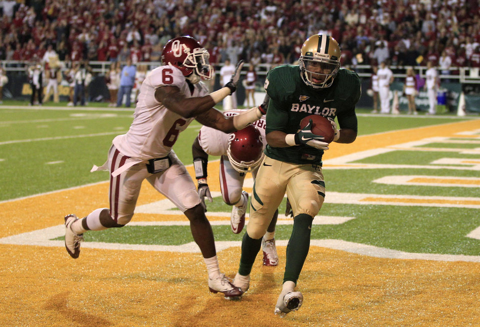 Photo - Baylor wide receiver Terrance Williams (2) comes down with a touchdown reception against Oklahoma defenders Ben Sherrard (6) and defensive back Sam Proctor (27) late in the second half of an NCAA college football game Saturday, Nov. 19, 2011, in Waco, Texas. The score gave Baylor the 45-38 win. (AP Photo/Tony Gutierrez)