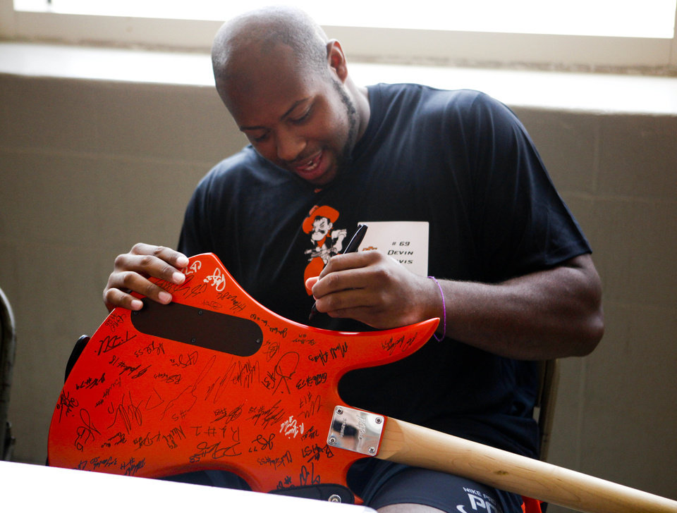 Photo - Oklahoma State offensive lineman Devin Davis signs a custom painted guitar owned by Kody Bickerstaff at fan appreciation day at Gallagher-Iba Arena on August 3, 2013. KT King, For The Oklahoman