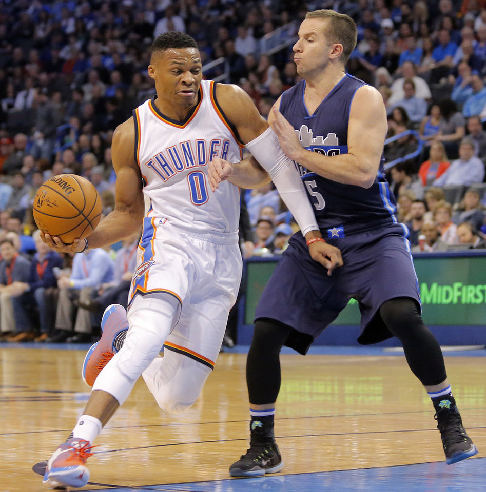 Photo - Oklahoma City's Russell Westbrook (0) drives past Dallas' J.J. Barea (5) during the NBA basketball game between the Oklahoma City Thunder and the Dallas Mavericks at Chesapeake Energy Arena on Wednesday, Jan. 13, 2016, in Oklahoma City, Okla.  Photo by Chris Landsberger, The Oklahoman