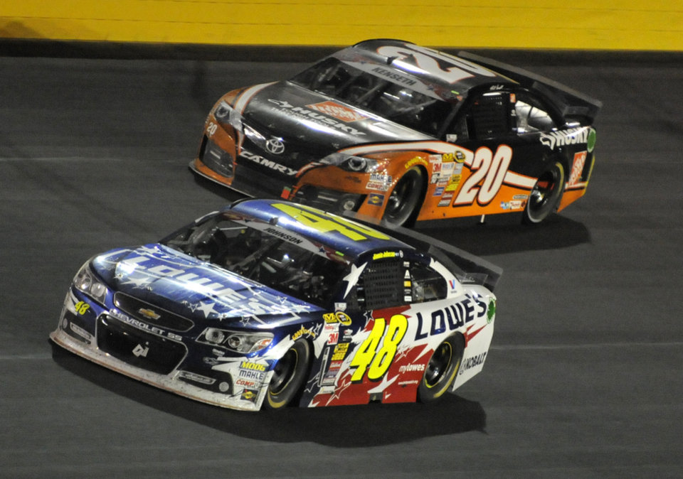 Photo - Jimmie Johnson (48) passes Matt Kenseth (20) for the lead in the closing laps of the NASCAR Sprint Cup series Coca-Cola 600 auto race at Charlotte Motor Speedway in Concord, N.C., Sunday, May 25, 2014. (AP Photo/Mike McCarn)