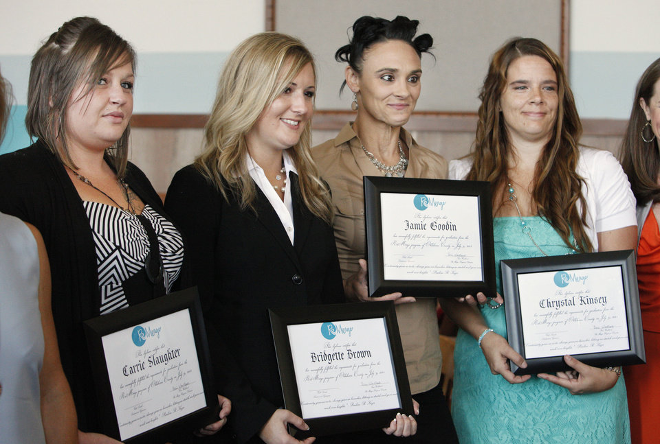 Photo - Graduates Carrie Slaughter, Okla. City, Bridgette Brown, Okla. City, Jamie Goodin, Okla, City, and Chrystal Kinsey, Moore, pose for a picture holding their graduation certificates during the ReMerge graduation ceremonies at the Oklahoma County Courthouse in Oklahoma City Tuesday, July 9, 2013. The ReMerge program is an alternative to prison for mothers and pregnant women who are facing charges for nonviolent crimes. Photo by Paul B. Southerland, The Oklahoman