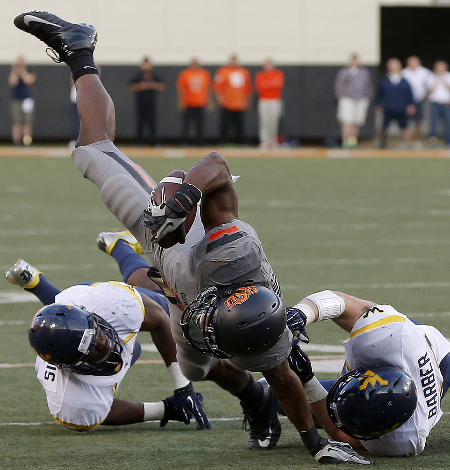 Photo - Oklahoma State's Joseph Randle (1) fights for more yards beside West Virginia's Jared Barber (33) during a college football game between Oklahoma State University (OSU) and West Virginia University at Boone Pickens Stadium in Stillwater, Okla., Saturday, Nov. 10, 2012. Oklahoma State won 55-34. Photo by Bryan Terry, The Oklahoman