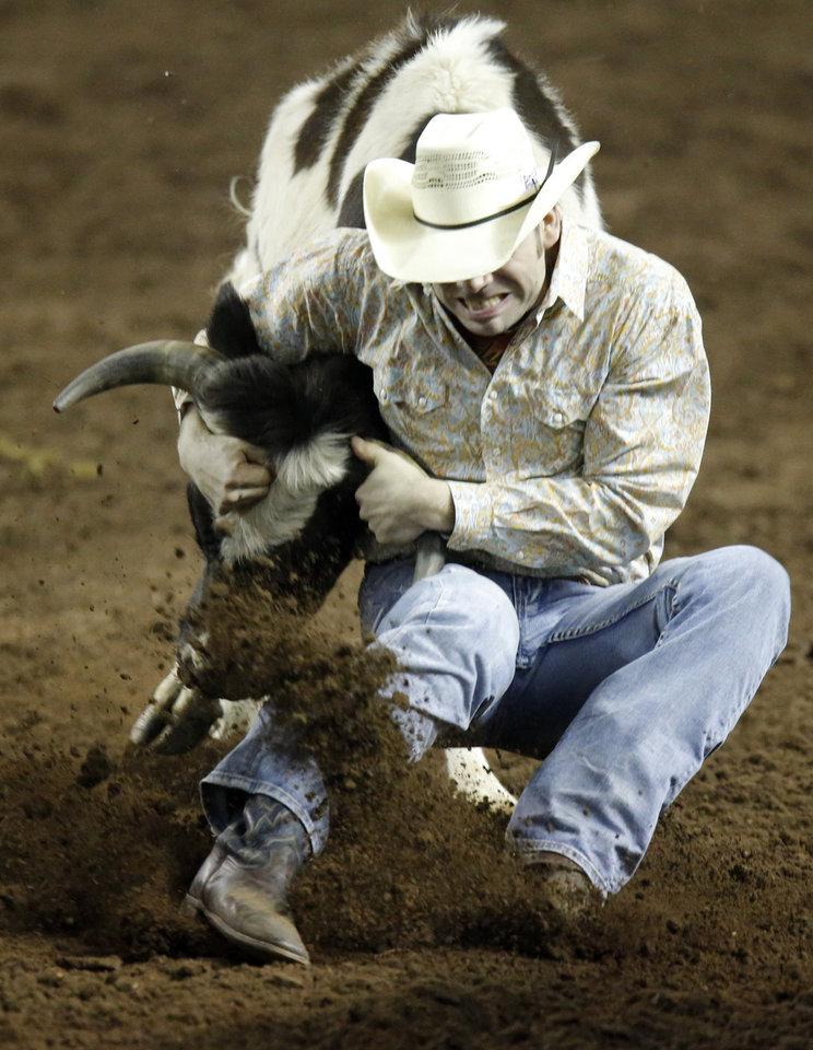 Matthew Mousseau of Dashwood Canada wrestles a steer during the steer wresting event at the International Finals Rodeo at the State Fair Arena in Oklahoma City,  Saturday, Jan. 19, 2013. Photo by Sarah Phipps, The Oklahoman