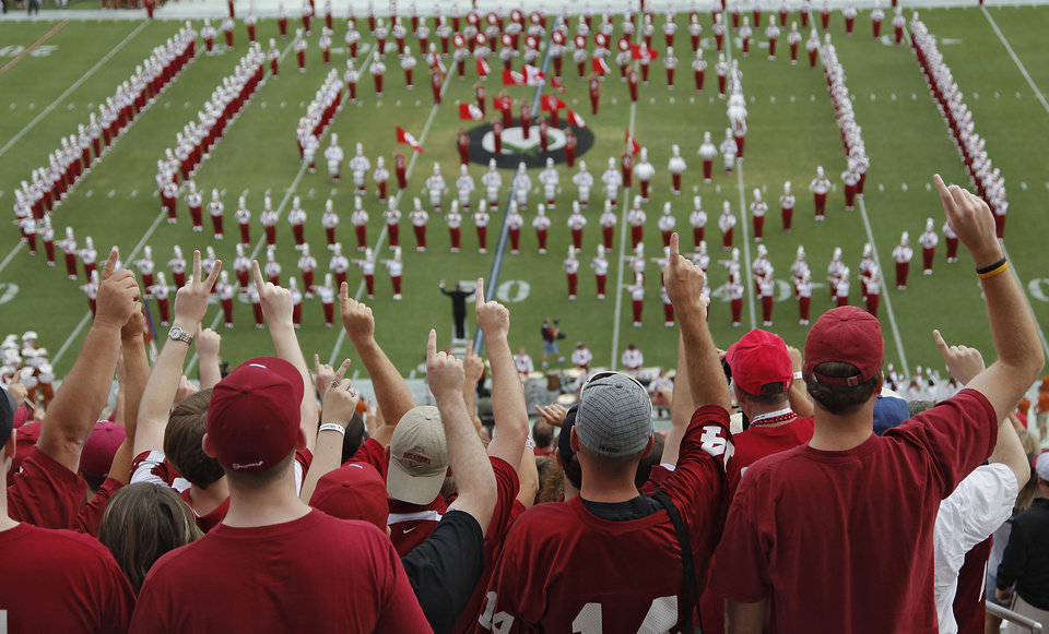 Photo - Oklahoma fans sing the school song performed by the Pride of Oklahoma band during the Red River Rivalry college football game between the University of Oklahoma Sooners (OU) and the University of Texas Longhorns (UT) at the Cotton Bowl in Dallas, Saturday, Oct. 8, 2011. Photo by Chris Landsberger, The Oklahoman
