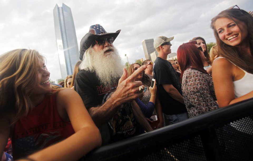 Photo - An older music fan dances as two younger women laugh while country artist Josh Abbott Band performs at OKC Fest in downtown Oklahoma City on Friday, June 27, 2014. OKC Fest is a new two day country music festival with multiple stages downtown. Photos by KT King/The Oklahoman