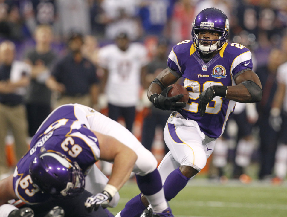 Photo - Minnesota Vikings running back Adrian Peterson, right, carries the ball during the first half of an NFL football game against the Chicago Bears Sunday, Dec. 9, 2012, in Minneapolis. (AP Photo/Genevieve Ross)