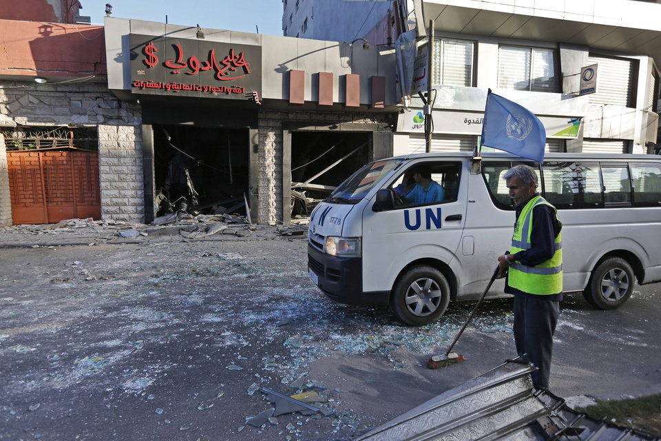 Photo - A Palestinian municipality worker sweeps the streets from glass, as a United Nations vehicle drives past a damaged money exchange post, following an overnight Israeli missile strike in Gaza City, Thursday, July 17, 2014. The Israeli military says it has struck 37 targets in Gaza ahead of a five-hour humanitarian cease-fire meant to allow civilians to stock up after 10 days of fighting. The Gaza Interior Ministry says four people were killed and that a 75-year-old woman died of wounds from the day before. The Israeli army says Hamas fired 11 rockets at Israel early Thursday. Palestinian health officials say that in total, at least 225 Palestinians have been killed. On the Israeli side, one man was killed since July 8.(AP Photo/Lefteris Pitarakis)