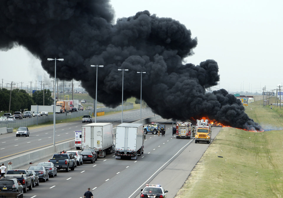 Photo - A northbound semi trailer loaded with roadway paint is a blaze as Interstate 35 is shut Wednesday, July 10, 2013 in Norman, Okla.  (AP Photo/The Oklahoman, Steve Sisney)