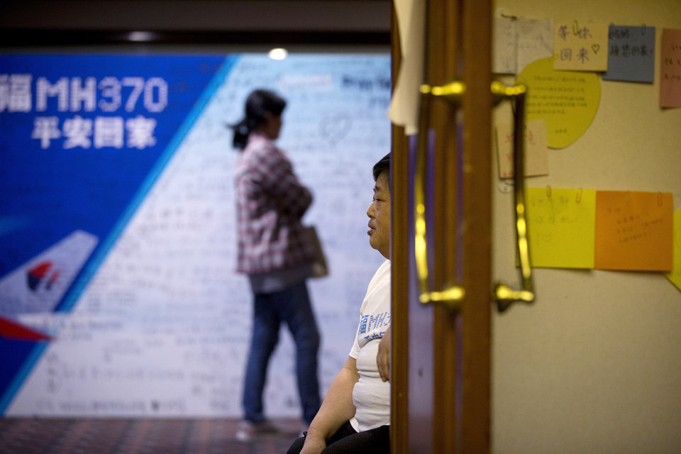 Photo - A woman, one of the relatives of Chinese passengers aboard the missing Malaysia Airlines flight MH370, sits on a chair near a poster with messages of wishes written on at a hotel in Beijing, China Tuesday, April 1, 2014. Although it has been slow, difficult and frustrating so far, the search for the missing Malaysia Airlines jet is nowhere near the point of being scaled back, Australia's Prime Minister Tony Abbott said. The three-week hunt for Flight 370 has turned up no sign of the Boeing 777, which vanished March 8 with 239 people bound for Beijing from Kuala Lumpur. (AP Photo/Andy Wong)