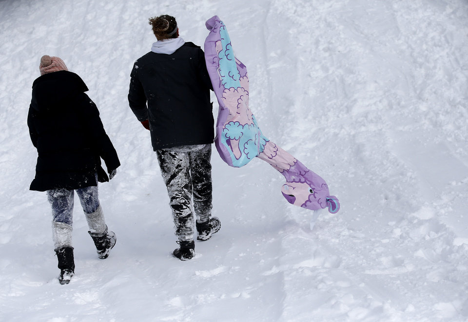 Photo - Anna Davidson and Jake Robertson walk up hill after sledding along Hefner Road in Oklahoma City, Wednesday, Feb. 17, 2021. [Sarah Phipps/The Oklahoman]