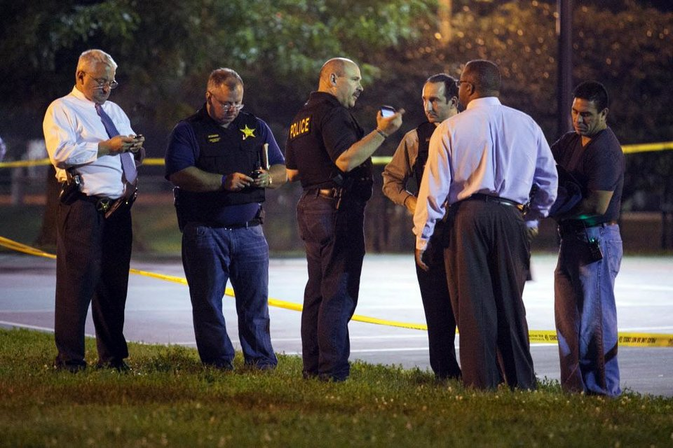 Photo - In this Thursday, Sept. 19, 2013, photo, officials convene near the scene of a shooting at Cornell Square Park in Chicago's Back of the Yard neighborhood that left multiple victims including a 3-year-old boy. Thursday night's attack was the latest violence in a city that has struggled to stop such shootings by increasing police patrols. (AP Photo/Sun-Times Media, Chandler West)