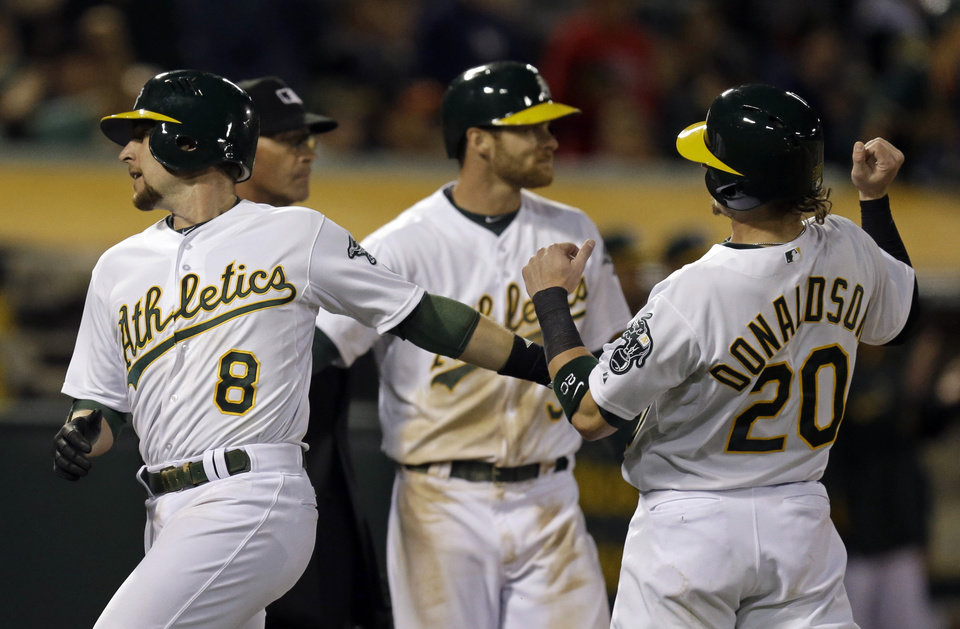 Oakland Athletics' Jed Lowrie, left, and Josh Donaldson (20) celebrate after both scored against the San Francisco Giants in the sixth inning of a baseball game Monday, July 7, 2014, in Oakland, Calif. Both scored on a double by Alberto Callaspo. (AP Photo/Ben Margot)