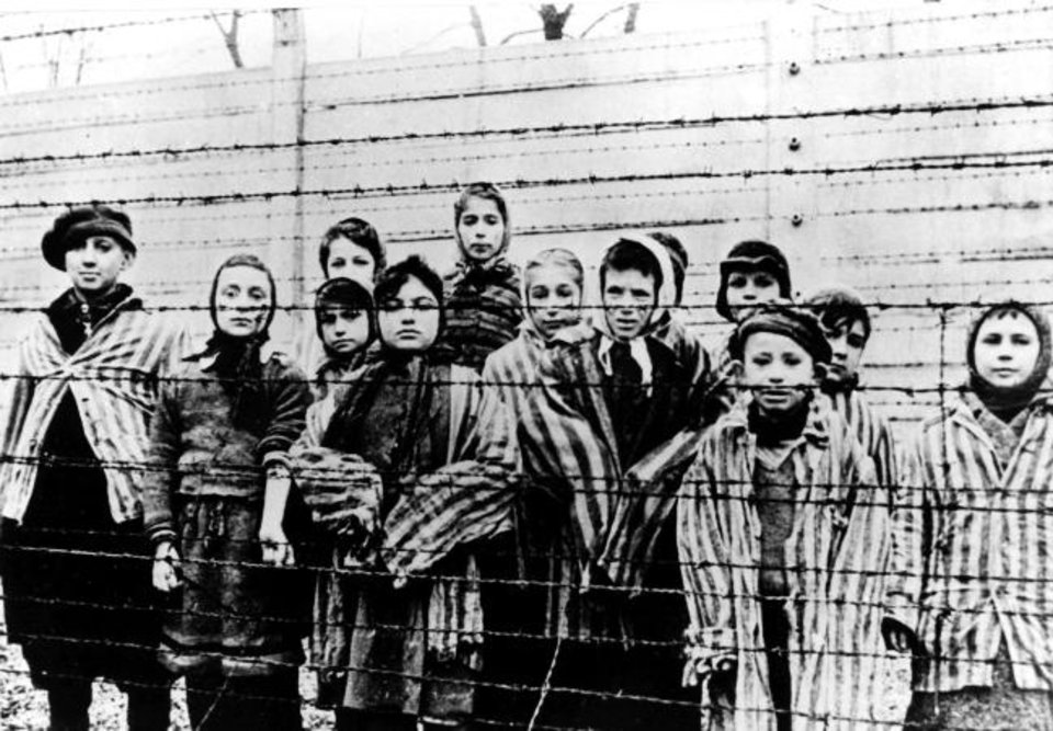 Photo -  In this file photo taken just after the liberation by the Soviet army in January 1945, a group of children wearing concentration camp uniforms are shown behind barbed wire fencing in the Auschwitz Nazi concentration camp. [AP File Photo]
