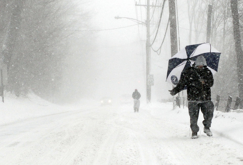 Photo - A man hitchhikes along route 63 as snow falls Thursday, Feb. 13, 2014, in Naugatuck, Conn.,  as a winter storm rolled through the area. (AP Photo/The Republican-American, Christopher Massa.)