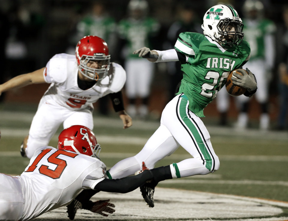 Photo - Irish running back Braden Roy slips a tackle attempt by Bo Bradshaw as the Bishop McGuinness Irish play the Carl Albert Titans in a Class 5A semi-final playoff game at Harve Collins Field on Friday, Nov. 23, 2012  in Norman, Okla. Photo by Steve Sisney, The Oklahoman