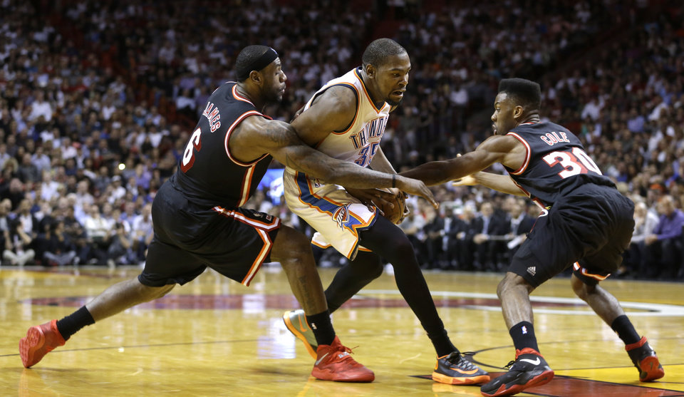 Photo - Miami Heat small forward LeBron James (6) and point guard Norris Cole (30) apply pressure on Oklahoma City Thunder small forward Kevin Durant (35) during the third period of an NBA basketball game in Miami, Wednesday, Jan. 29, 2014. The Thunder won 112-95.  (AP PhotoAlan Diaz)