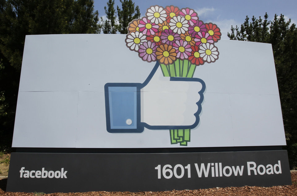 Photo - Flowers were added to a Facebook sign Sunday in front of Facebook headquarters in Menlo Park, Calif. AP Photo
