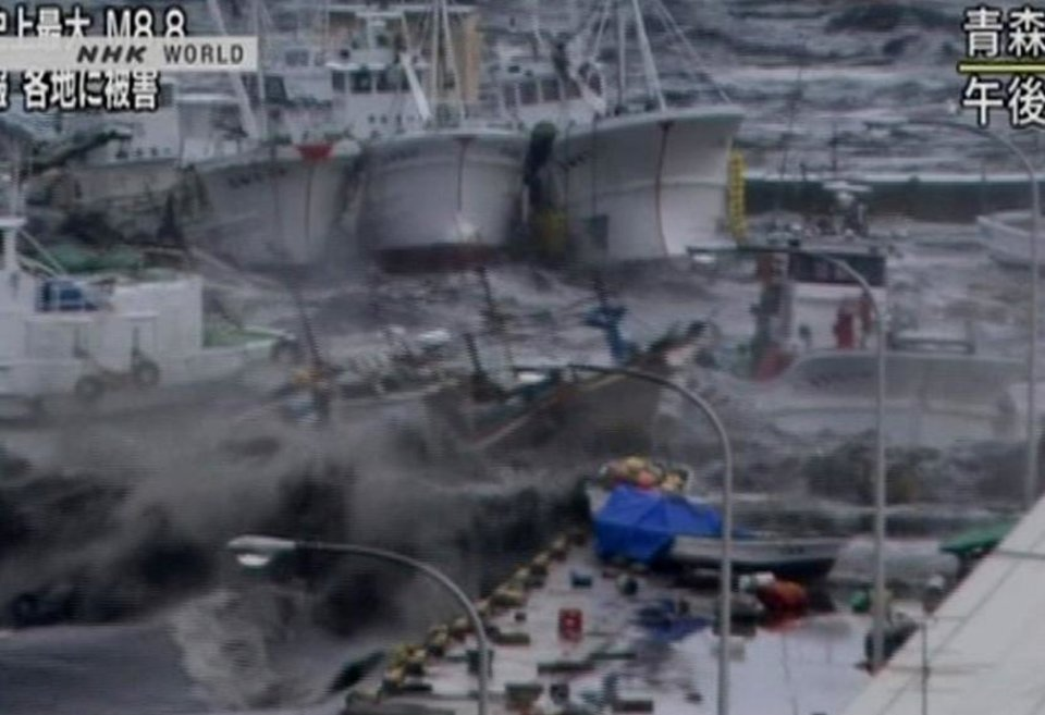 Photo - In this video image taken from Japan's NHK TV, a tsunami surge throws boats against a building in Hachinoche, Aomori Prefecture, Japan Friday March 11, 2011 following a massive earth quake. A magnitude 8.9 earthquake slammed Japan's northeastern coast Friday, unleashing a 13-foot (4-meter) tsunami that swept boats, cars, buildings and tons of debris miles inland. Fires triggered by the quake burned out of control up and down the coast.  (AP PHOTO/NHK TV) MANDATORY CREDIT, JAPAN OUT, TV OUT,  NO SALES, EDITORIAL USE ONLY ORG XMIT: LON833