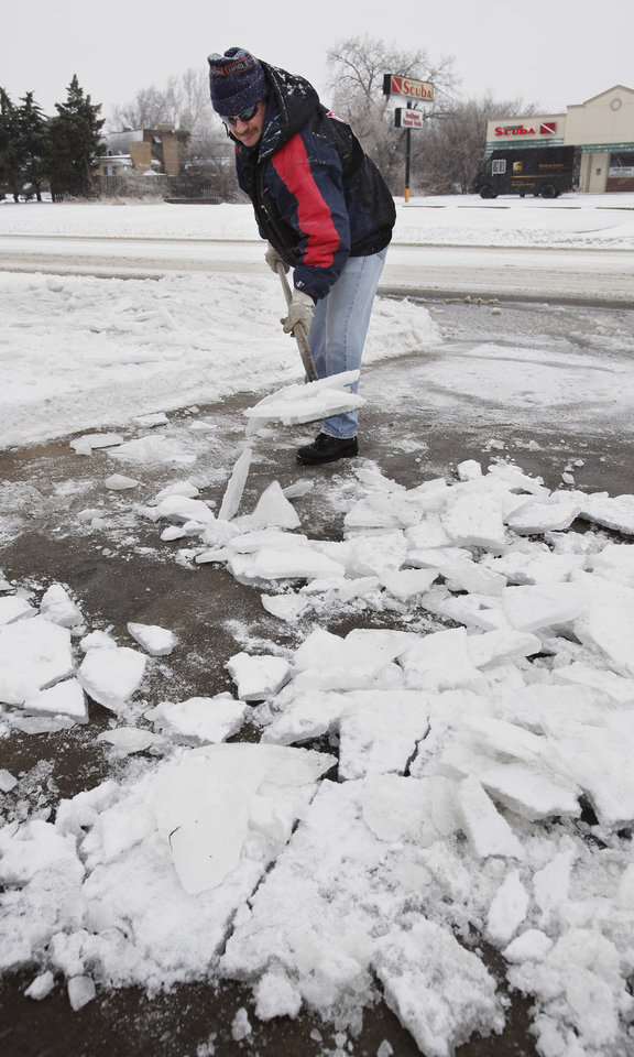 Photo - Dave Mills, apartment resident, shovels ice from the entrance to Pheasant Run Apartments in the 6100 block of N. Meridian in Oklahoma City Friday, Jan. 29, 2010. Photo by Paul B. Southerland, The Oklahoman ORG XMIT: KOD