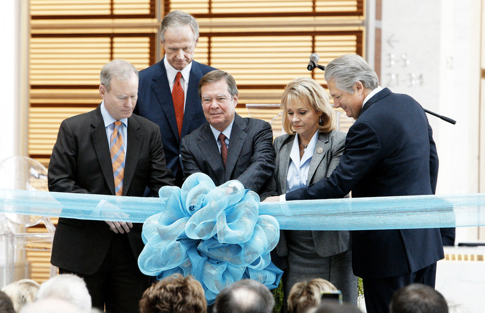 Photo - Larry Nichols, center, Devon Energy Corp. executive chairman, pulls a pin on a ribbon Tuesday at the Devon Energy Center in Oklahoma City. From left are Mayor Mick Cornett, Devon President and CEO John Richels, Nichols, Gov. Mary Fallin and building architect Jon Pickard. After six years of planning and three years of construction, Devon Energy held a ceremony commemorating completion of the center.  Photo by Paul B. Southerland, The Oklahoman