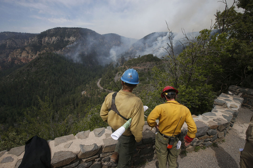 Photo - True Brown, left, of the Blue Ridge Hotshots, and Mark Adams, of the Mormon Lake Hotshots, take a high vantage point as spotters for those fighting the the Slide Fire below as it burns up Oak Creek Canyon on Friday, May 23, 2014, near Flagstaff, Ariz.  The fire has burned approximately 7,500 acres and is five percent contained. (AP Photo/Ross D. Franklin)