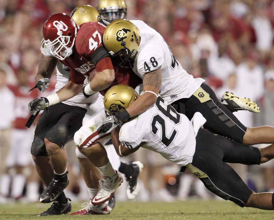Photo - OU's Trent Ratterree fights off Colorado's Liloa Nobriga, top, and Ray Polk during the college football game between the University of Oklahoma (OU) Sooners and the University of Colorado Buffaloes at Gaylord Family-Oklahoma Memorial Stadium in Norman, Okla., Saturday, October 30, 2010. Photo by Bryan Terry, The Oklahoman