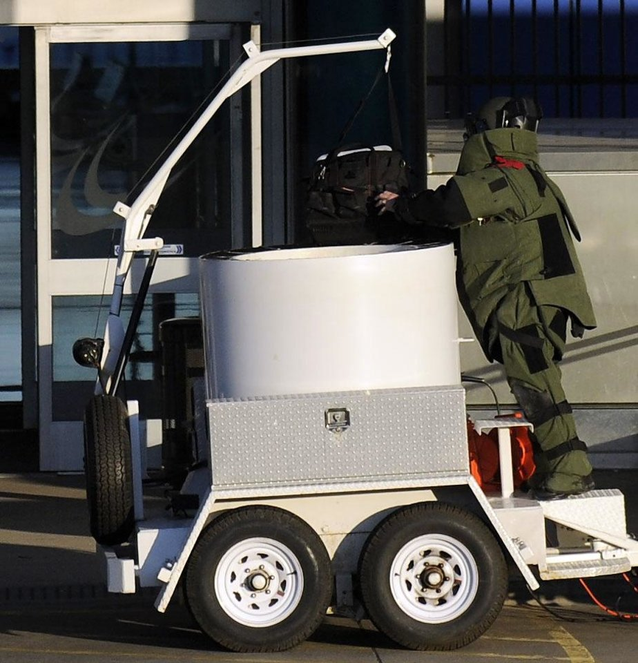 Photo - The bomb squad removes a piece of luggage at a closed down North Terminal at the Detroit Metropolitan Airport in Romulus, Mich., Monday April 1, 2013.  Authorities evacuated the smaller of two terminals at the airport for about two hours and detained one person as a bomb squad responded to a suspicious item at a security checkpoint.  (AP Photo/Detroit News, David Coates)  DETROIT FREE PRESS OUT; HUFFINGTON POST OUT
