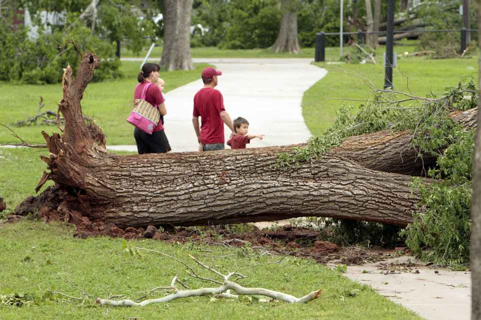 Photo - A family walks through Abe Andrews Park looking at damage caused by Friday's tornado. PHOTO BY STEVE SISNEY, THE OKLAHOMAN  STEVE SISNEY