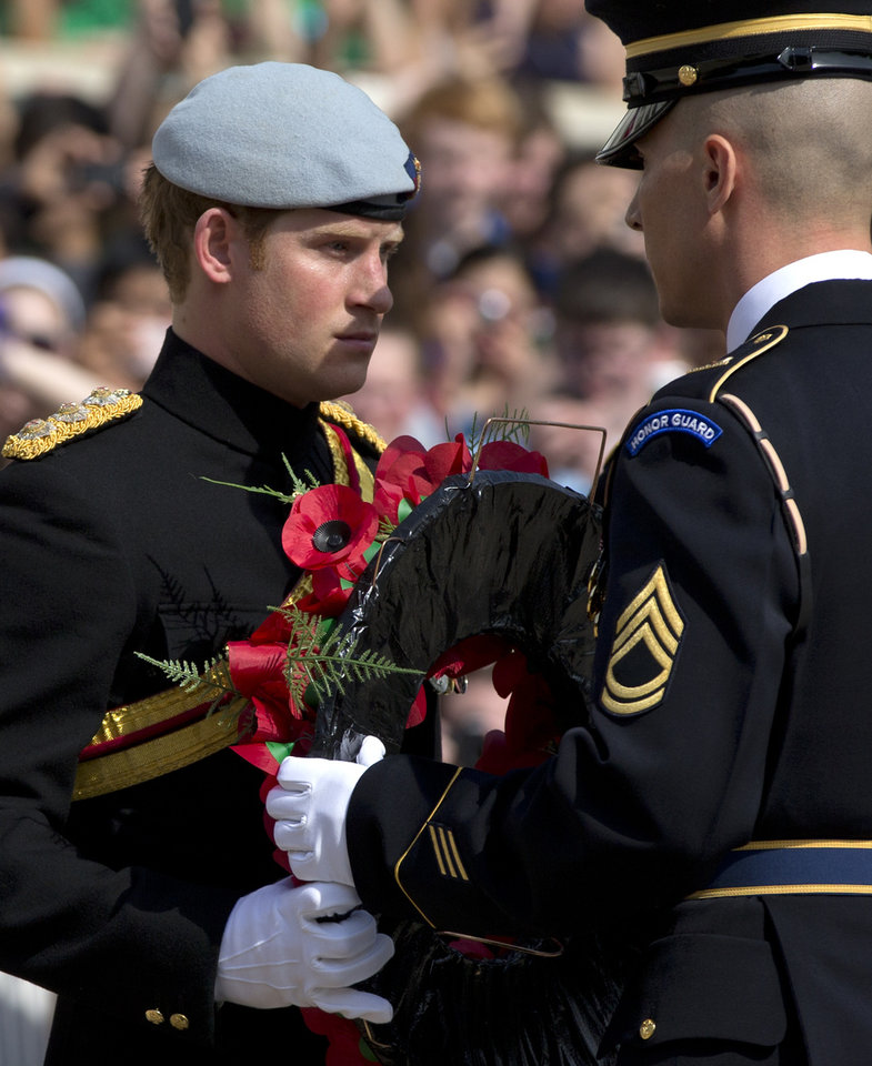 Photo - Britain's Prince Harry accepts a wreath from a member of The Old Guard during a wreath laying ceremony at the Tomb of the Unknowns at Arlington National Cemetery in Arlington, Va Friday, May 10, 2013. (AP Photo/Carolyn Kaster)