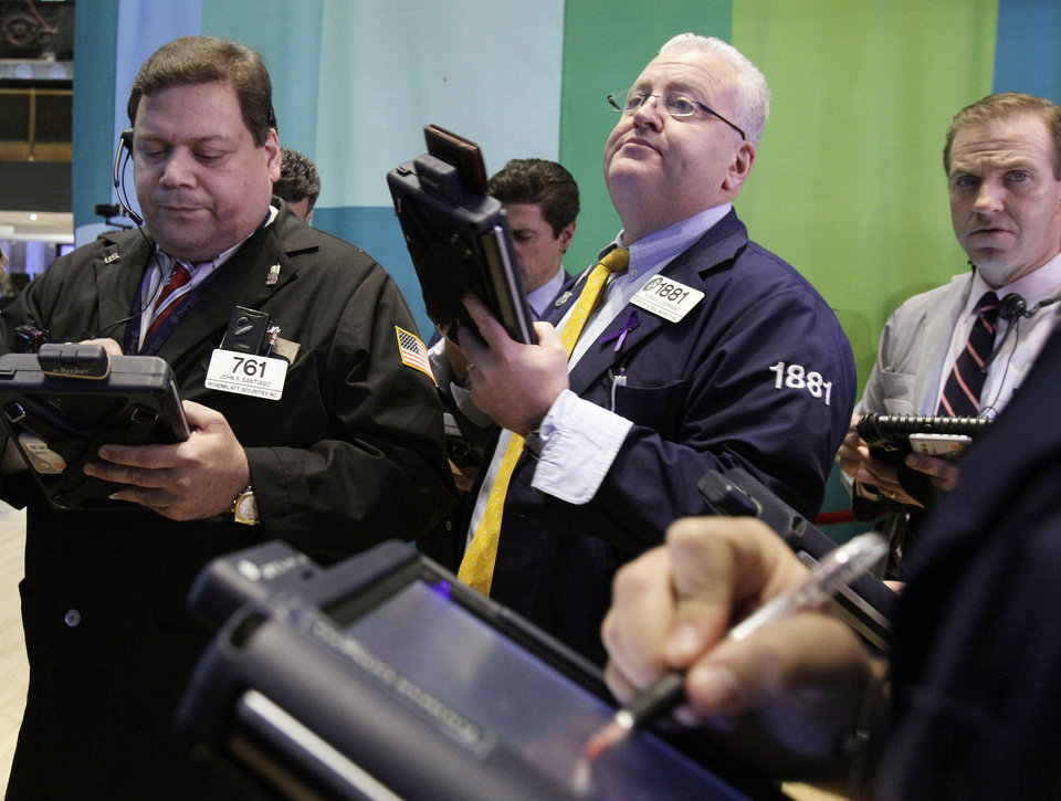 Photo - Traders work on the floor of the New York Stock Exchange Tuesday, Dec. 11, 2012. Stocks opened higher Tuesday ahead of a meeting of the Federal Reserve and possible additional steps to bolster the U.S. economy.  (AP Photo/Richard Drew)