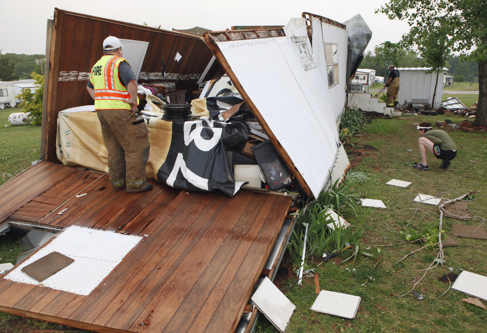 Photo - Firemen help Meshelle Reed look for her missing dog Lexi after storm damaged her home in the Priarie Creek Village mobile home park on Monday, May 10, 2010, in Noble, Okla.  Photo by Steve Sisney, The Oklahoman