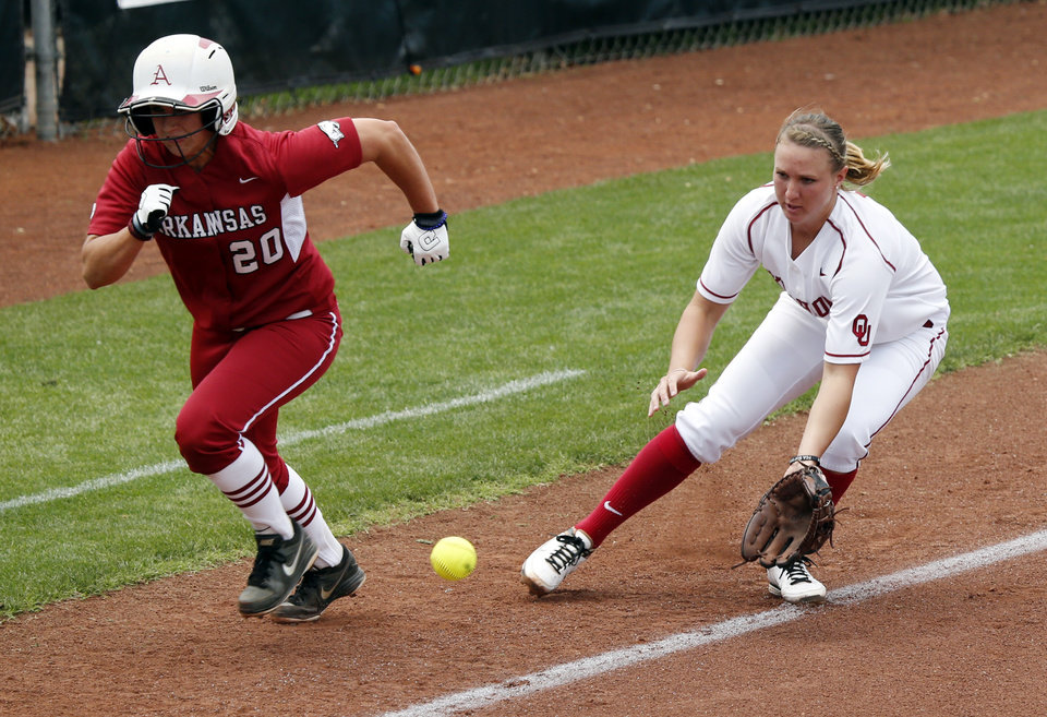 Photo - Sooner third baseman Shelby Pendley catches a ground ball as Arkansas's Chloe Oprzedek runs past at the Norman Regional of the 2013 NCAA Division I Softball Women's College World Series as the University of Oklahoma (OU) Sooners play the Arkansas Razorbacks at Marita Hines Field on Saturday, May 18, 2013  in Norman, Okla. Photo by Steve Sisney, The Oklahoman