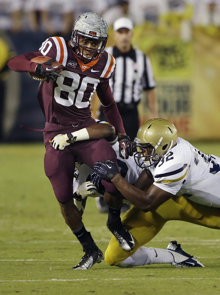 Photo - Virginia Tech wide receiver Demitri Knowles (80) is stopped by Georgia Tech linebacker Paul Davis (40) and linebacker Jabari Hunt-Days (32) in the first half of an NCAA college football game on Thursday, Sept. 26, 2013 in Atlanta. (AP Photo/John Bazemore)