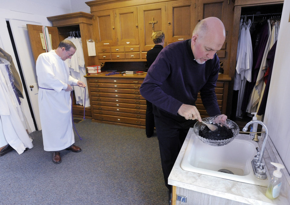 The Rev. Carl McCarthy, right, stirs in water into a bowl of palm ashes while server Ron Daugherty dresses in a vestment, Wednesday, Feb. 22, 2012, before the Ash Wednesday service at SS. Joseph & Paul Catholic Church in Owensboro, Ky. Last year's palms from Palm Sunday were burned and used to mark the foreheads of parishioners. Blessed items are never thrown away; they are returned to the earth, a parishioner said.  (AP Photo/The Messenger-Inquirer, John Dunham)