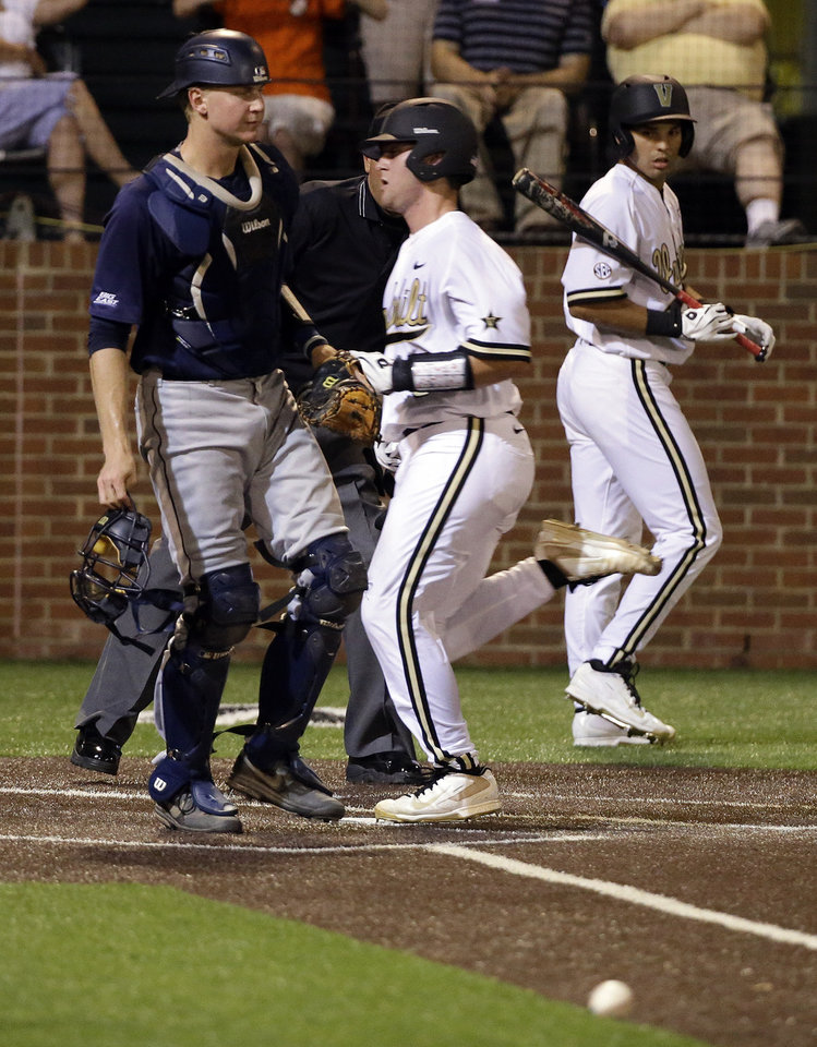 Photo - Vanderbilt's Jason Delay, center, scores as the ball bounces off the wall on a wild pitch as Xavier catcher Daniel Rizzie, left, watches during the fifth inning of an NCAA college baseball tournament regional game Friday, May 30, 2014, in Nashville, Tenn. At right is Vanderbilt batter Vince Conde. (AP Photo/Mark Humphrey)
