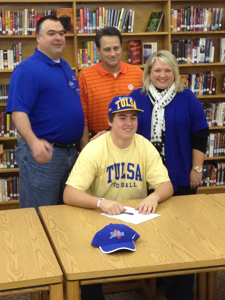Photo - Norman's Zac Uhles poses for a photo with, from left, his father Rob, Norman coach Greg Nation and his mother, Charla. Uhles signed to play football at Tulsa. PHOTO PROVIDED