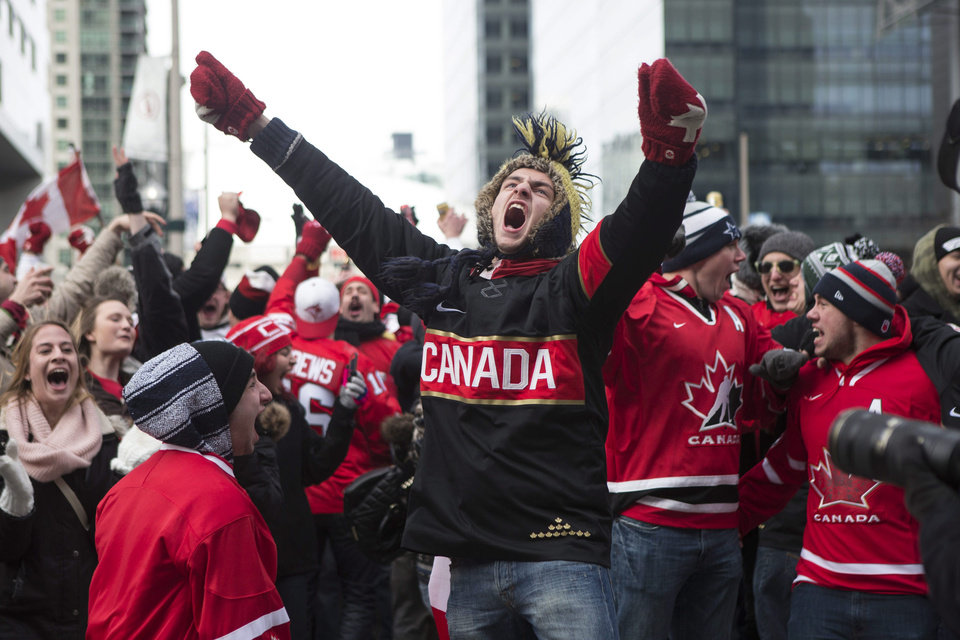 Photo - Hockey fans celebrate in Toronto's Maple Leaf Square after the final buzzer as Canada beat Sweden 3-0 to win the Gold Medal in the men's Olympic Hockey Final on Sunday, Feb. 23, 2014. (AP Photo/The Canadian Press, Chris Young)
