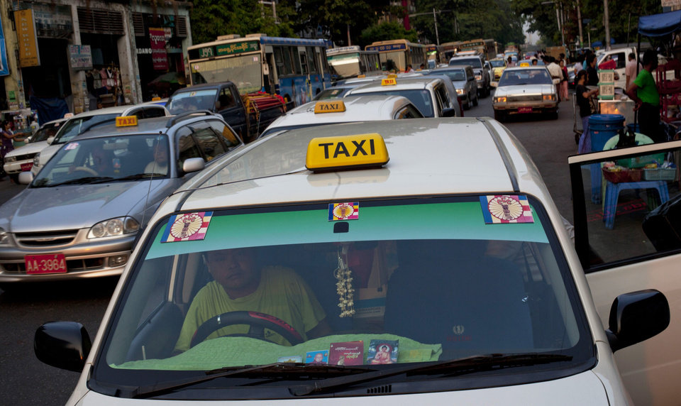 A taxi with 969 logos on the windshield stops for a passenger in Yangon, Myanmar on March 31, 2013. (AP Photo/Gemunu Amarasinghe)