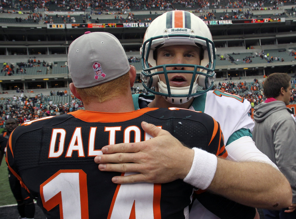 Photo -   Miami Dolphins quarterback Ryan Tannehill, right, hugs Cincinnati Bengals quarterback Andy Dalton (14) after the Dolphins defeated the Bengals 17-13 in an NFL football game on Sunday, Oct. 7, 2012, in Cincinnati. (AP Photo/Tom Uhlman)